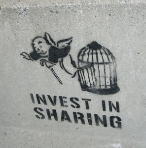 """Grafito en una calle de Toronto, con la leyenda """"Invest in sharing"""". Fotografía de Toban Black."""