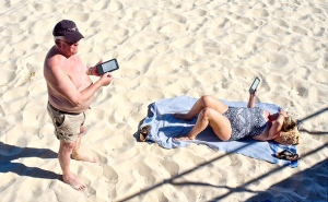 Pareja de lectores con dispositivos Kindle en la playa.